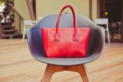 时尚和时髦样式大红色提包设计师在一把美丽的椅子站立由在一个夏天咖啡馆的塑料制成在 免版税库存图片