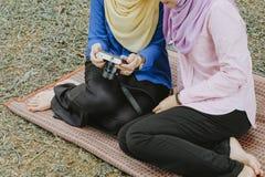 时尚和生活方式概念,与hijab的年轻muslimah坐草和预览他们的在袖珍相机的照片 免版税图库摄影