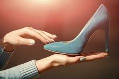 时尚和秀丽、购物和介绍,灰姑娘 有魅力女性鞋子蓝色颜色绒面革的手 库存照片