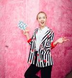 时尚在时髦的镶边衬衣和红色长裤姿势打扮的少女博客作者在桃红色毛皮墙壁背景  免版税库存照片