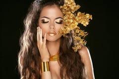 时尚在黑背景隔绝的秀丽女孩。构成。金黄 免版税库存图片