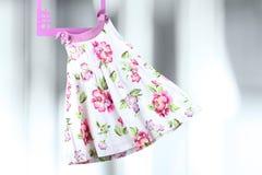 时尚垂悬在灰色背景的一个挂衣架的婴孩礼服 免版税图库摄影