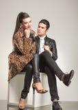 时尚夫妇坐一个白色立方体 免版税库存图片