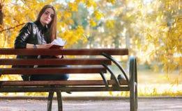 时尚女孩读了书长凳 免版税库存图片
