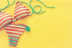 时尚女性泳装比基尼泳装顶视图在黄色木背景的 图库摄影