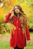 年轻时尚妇女在红色外套穿戴了在秋天公园 免版税库存图片
