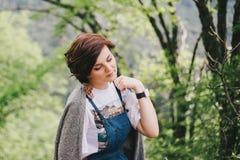 年轻时尚妇女坐一块石头有后边美好的山景 免版税库存照片