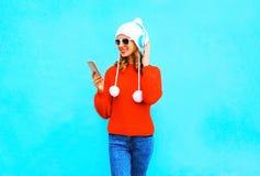 时尚妇女用途智能手机听到在无线耳机的音乐在红色毛线衣 图库摄影