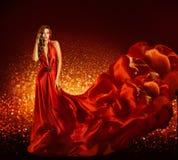 时尚妇女红色礼服,秀丽式样褂子飞行的丝织物 免版税库存照片