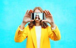 时尚妇女采取在智能手机的图片自画象在蓝色 图库摄影