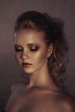 年轻时尚妇女面孔魅力画象与金黄明亮的晚上补偿党和被晒黑的皮肤 温暖定调子 reuben 免版税图库摄影