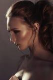 年轻时尚妇女面孔魅力画象与金黄明亮的晚上补偿党和被晒黑的皮肤 温暖定调子 reuben 免版税库存图片