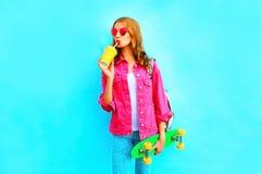 时尚妇女饮料果汁拿着穿桃红色牛仔布夹克的滑板 库存图片