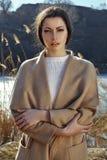 时尚妇女画象室外米黄的外套的 免版税图库摄影