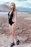 时尚射击的美丽的性感的逗人喜爱的女孩在沙漠干燥破裂的地球的游泳衣在山的背景中 免版税库存图片