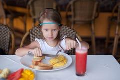 时尚小女孩吃早餐在手段 免版税库存照片