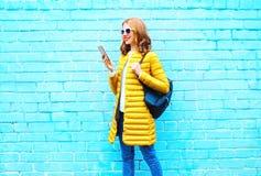 时尚少妇使用在一块蓝色砖的智能手机步行 免版税库存图片