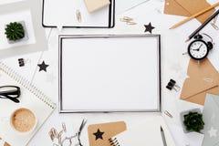 时尚工作区背景 框架、咖啡、办公用品、闹钟和笔记本在白色桌面看法 平的位置 复制空间 免版税库存照片