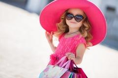 时尚帽子的逗人喜爱的小女孩有在超级市场旁边的购物袋的 图库摄影