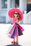 时尚帽子的逗人喜爱的小女孩有在超级市场旁边的购物袋的 库存照片
