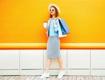 时尚微笑的妇女拿着一个咖啡杯,穿草帽的购物袋 库存图片