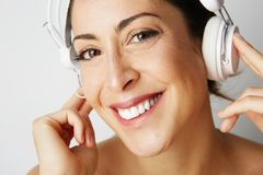 时尚愉快的凉快的女孩画象被剥离对在听到在空的白色的音乐的白色耳机的腰部 图库摄影