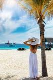 时尚旅行家妇女在一个热带海滩站立 免版税库存照片