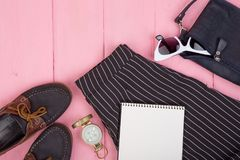 时尚材料-袋子,长裤,太阳镜,指南针,鞋子,在桃红色木背景的空白的笔记本 库存照片