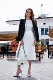 时尚样式街道看起来典雅的深色的妇女步行咖啡馆resta 免版税库存照片