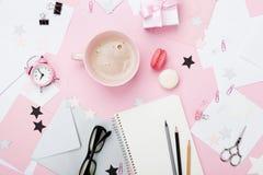 时尚桃红色妇女工作场所背景 咖啡、macaron、办公用品、礼物和干净的笔记本在淡色桌面看法 免版税库存图片