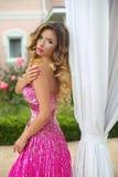 时尚桃红色礼服的美丽的白肤金发的式样女孩有构成的和 库存图片