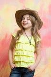 时尚牛仔帽的美丽的小女孩有愉快的面孔 免版税库存照片