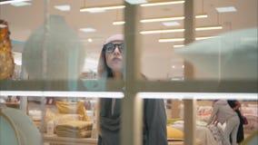 时尚玻璃的一名年轻行家妇女进入有陈列室的商店 免版税图库摄影
