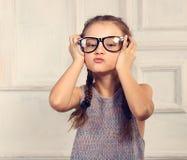 时尚玻璃的愉快的做鬼脸的孩子女孩与乐趣情感f 免版税库存图片