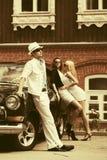 年轻时尚男人和妇女在葡萄酒汽车旁边 库存图片