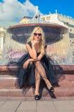 时尚白肤金发的女孩坐长凳在喷泉附近 街道Fashi 库存图片