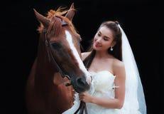 时尚白色婚礼服装立场的年轻美丽的秀丽新娘与在黑背景的英俊的马 免版税库存照片