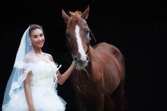 时尚白色婚礼服装立场的年轻美丽的秀丽新娘与在黑背景的英俊的马 库存图片
