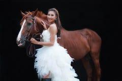 时尚白色新娘婚礼服装的年轻美丽的秀丽新娘支持在黑背景的英俊的马 免版税库存图片