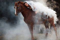 时尚白色新娘婚礼服装骑马的美丽的秀丽新娘在黑梦想的背景的强的肌肉马 库存照片