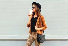 时尚相当少妇喝佩带一个减速火箭的典雅的帽子、太阳镜、棕色夹克和黑提包的杯子咖啡 库存照片