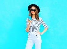 时尚相当少妇在城市使用佩带在五颜六色的蓝色背景的一个智能手机一台黑帽会议和提包传动器 库存图片