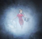时尚礼服的少妇在魅力背景 免版税图库摄影