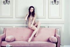 时尚礼服的年轻俏丽的深色的女孩在摆在lu的沙发 库存图片