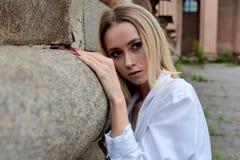 时尚神色的妇女 年轻女人现代画象 在白色裙子和衬衣打扮的年轻女人摆在老大厦附近 库存照片