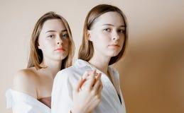 时尚秀丽模型看照相机的两个姐妹孪生美丽的裸体女孩隔绝在米黄背景 库存照片