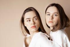 时尚秀丽模型看照相机的两个姐妹孪生美丽的裸体女孩隔绝在米黄背景 免版税库存图片