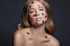 时尚秀丽魅力女孩 在她的头发的多彩多姿的金属星 免版税图库摄影