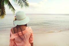 时尚穿草帽的愉快的年轻美丽的妇女画象后方-站立在海滩在夏天 库存图片