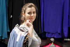 时尚精品店的女孩得到了衣裳并且去化装室 背景袋子概念行程购物的白人妇女 可爱的少妇在商店选择衣裳 免版税库存照片
